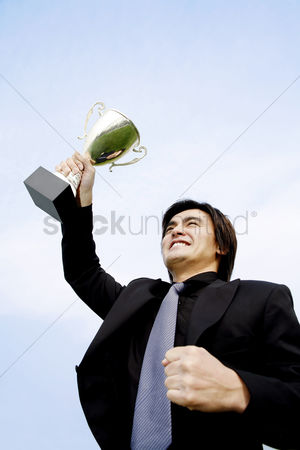 Motivation business : Businessman showing off his trophy