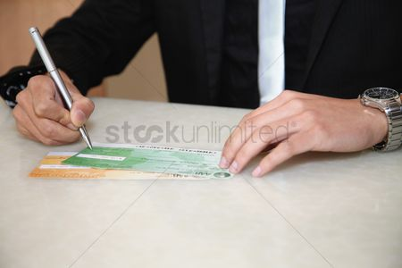 Spending money : Businessman signing cheque with pen