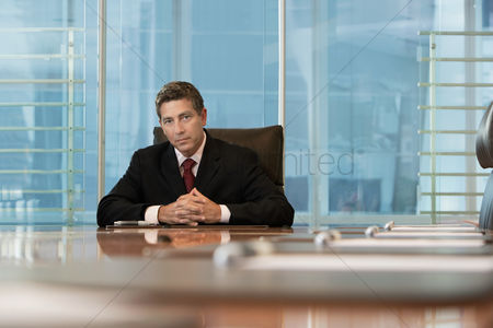 Leadership : Businessman sitting at conference table portrait