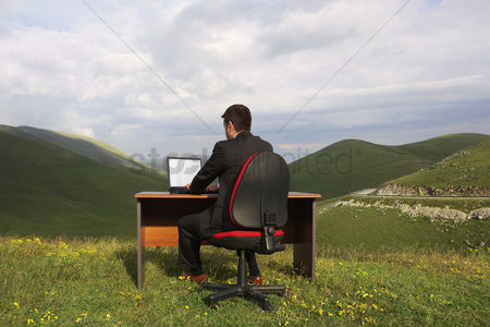 Remote : Businessman sitting at desk using laptop in mountain field back view