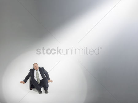 Pressure : Businessman sitting looking up at source of spotlight