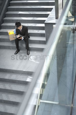 Firing : Businessman sitting on staircase writing on organizer