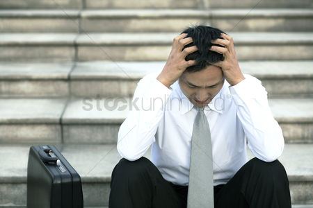 Three quarter length : Businessman sitting on the stairs with his hands on the head