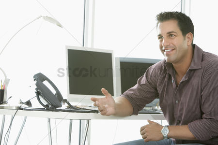 Appearance : Businessman smiling by computers in office