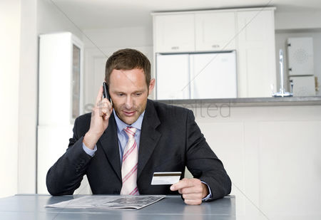 Cellular phone : Businessman talking on the mobile phone and holding credit card