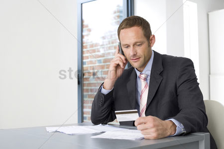 Cell phone : Businessman talking on the mobile phone and holding credit card