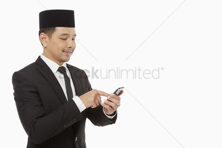 Portability : Businessman text messaging on his mobile phone
