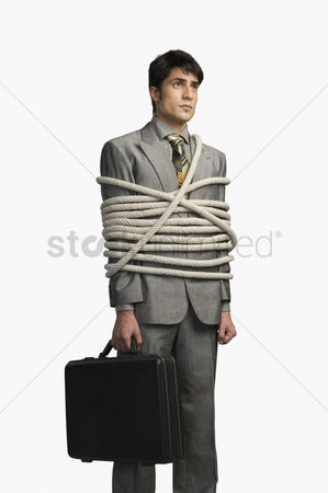 Forbidden : Businessman tied up with ropes and holding a briefcase