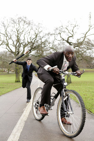 Trees : Businessman trying to beat another businessman with an umbrella
