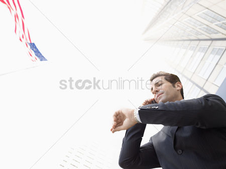 Flag : Businessman using mobile phone checking watch outdoors  low angle view