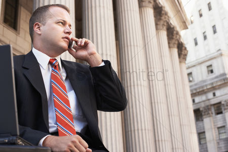 Worry : Businessman using mobile phone outside courthouse