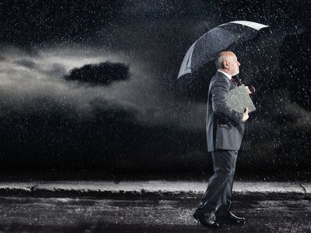 Cloud : Businessman walking in rain under umbrella side view
