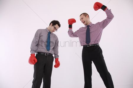 Loss : Businessman with boxing gloves celebrating after defeating his opponent