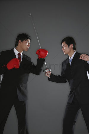 Fight : Businessman with boxing gloves challenging businessman with a fencing foil