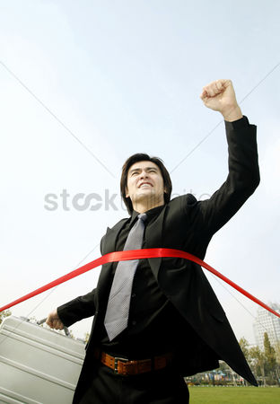 Celebrating : Businessman with briefcase running to the finishing line