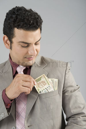 Pocket : Businessman with indian five hundred rupee banknotes in his pocket