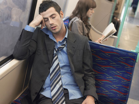 Transportation : Businessman with loosened tie sleeping on commuter train