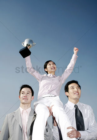 Motivation business : Businessmen lifting up a female winner