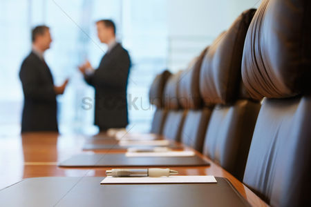 Two people : Businessmen talking in conference room