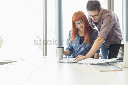 Showing : Businesspeople analyzing file together at desk in creative office