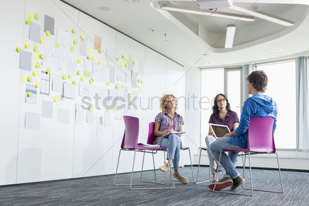 Creativity : Businesspeople discussing in creative office space