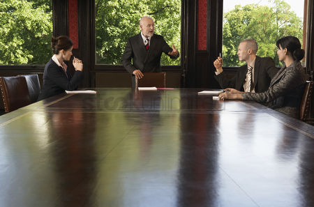 Maturity : Businesspeople meeting around boardroom table businessman standing