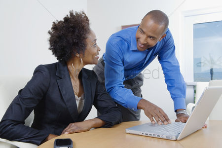 Two people : Businesspeople using laptop during meeting