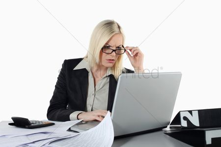 Frowning : Businesswoman adjusting glasses while using laptop