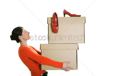 Strong : Businesswoman carrying boxes with her high heels on top