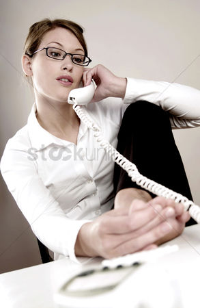 Bespectacled : Businesswoman checking her toes while talking on the phone