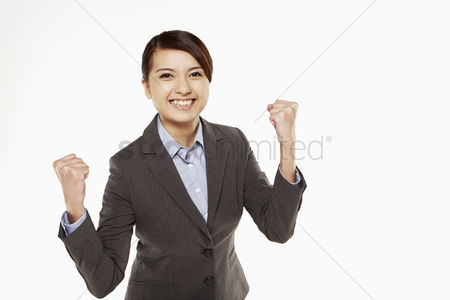 Three quarter length : Businesswoman cheering with fists in the air