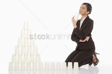 Malaysian indian : Businesswoman contemplating while arranging disposable cups