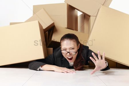Pressure : Businesswoman crying for help while being buried under a pile of boxes