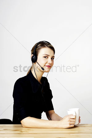 Answering calls : Businesswoman holding a cup of coffee while answering calls