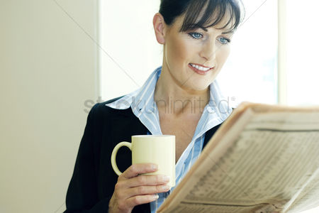 Smile : Businesswoman holding a cup of coffee while reading newspaper