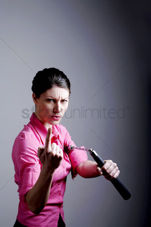 Fight : Businesswoman holding a nunchaku inviting people for a challenge