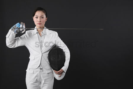 Fight : Businesswoman holding fencing mask and a fencing foil