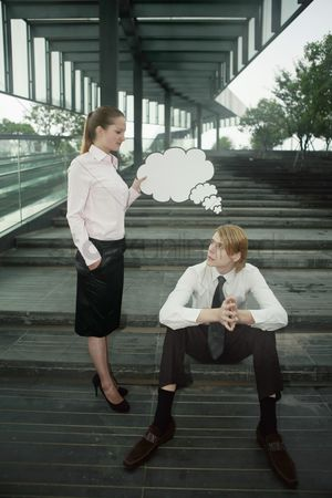 Cardboard cutout : Businesswoman holding thinking bubble above businessman s head