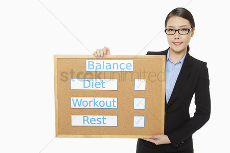 Workout : Businesswoman holding up a notice board
