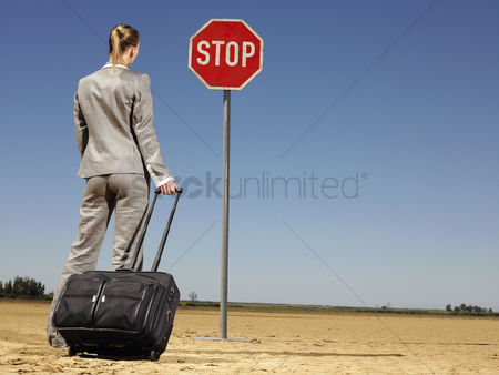 Business suit : Businesswoman in desert looking at stop sign