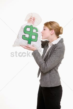 Kissing : Businesswoman kissing money bag