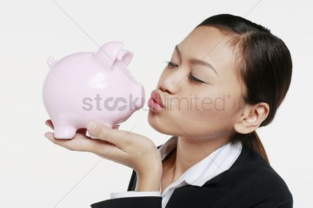 Kissing : Businesswoman kissing piggy bank