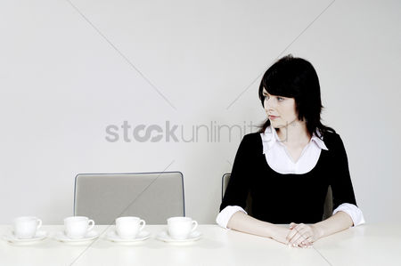 Wondering : Businesswoman looking at an arrangement of coffee cups