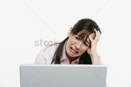 Head shot : Businesswoman looking stressed while using laptop