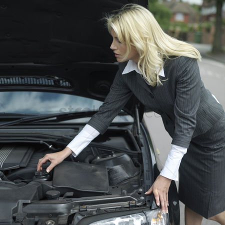 Fixing : Businesswoman looking under car hood