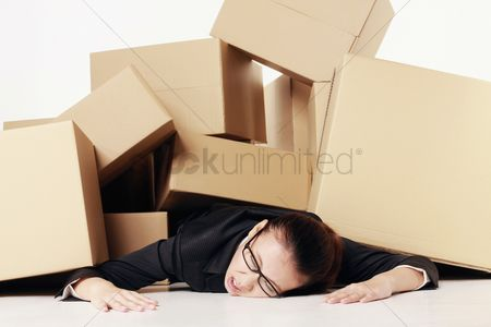 Lying forward : Businesswoman lying unconsciously on the floor after being buried under a pile of boxes