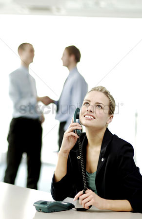 Client : Businesswoman on the phone while businessmen shaking hands on the background