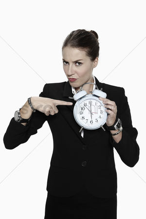 Frowning : Businesswoman pointing at alarm clock