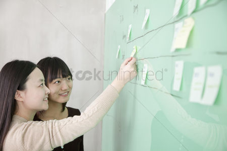 Advice : Businesswoman putting a stick note on the board  another businesswoman looking at the board
