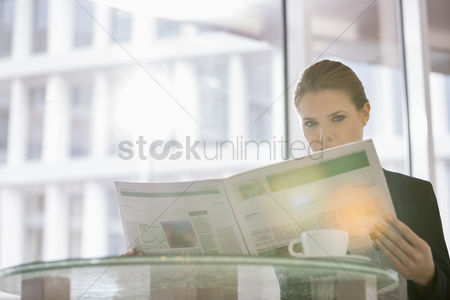 Media : Businesswoman reading newspaper at office cafe